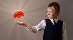 Image of a boy holding a 3D hologram of a brain in his hand