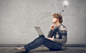 photo illustration of a student sitting on the ground with a laptop on his lap with a light bulb above his head (branding picture for Toolbox for Learning Receptiveness Profile™ Student Performer or LRP™ Student Performer)
