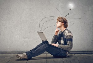 photo illustration of a student sitting on the ground with a laptop on his lap with a light bulb above his head