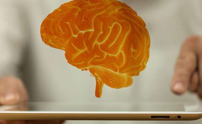 Hologram of a brain above an iPad (branding picture for educational development)